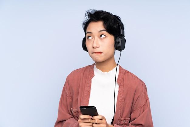 Menina asiática nova sobre música de parede isolada azul com um celular e pensamento