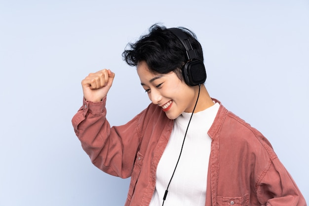 Menina asiática nova sobre música e dança de parede azul isolada