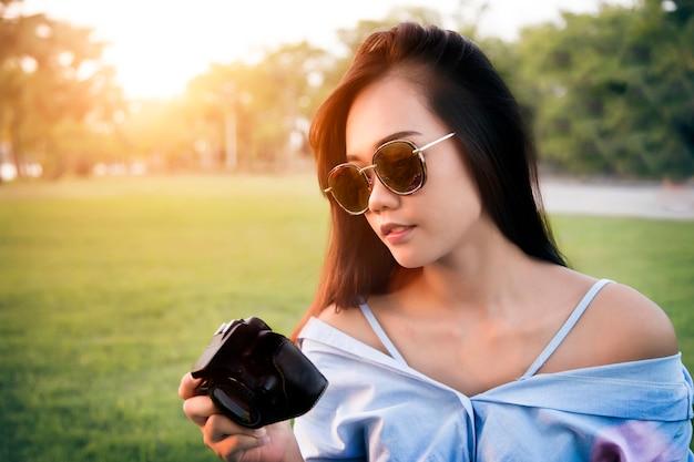 Menina asiática olha câmera digital