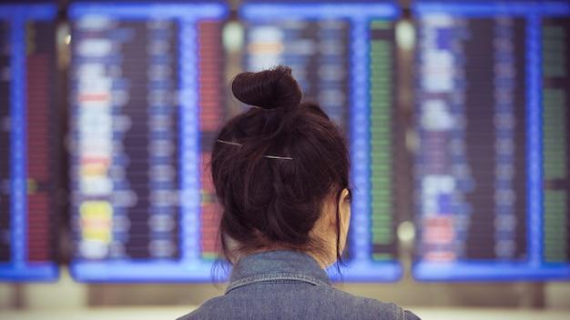 Menina asiática olhando a programação de voo no terminal do aeroporto, conceito único viajante