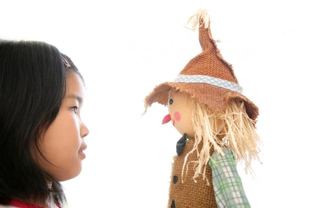 Menina asiática olhando seu brinquedo espantalho