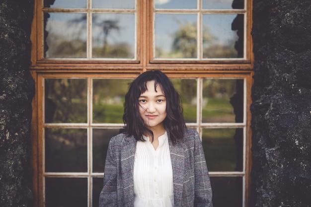 Menina asiática otimista em frente ao prédio rústico