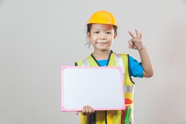 Menina asiática ou crianças em camisa azul e capacete de segurança amarelo em pé e segurando o quadro na mão