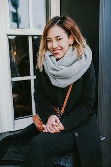 Menina asiática parece em casacos nos sorrisos de rua