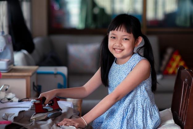 Menina asiática passando roupa na casa com um sorriso