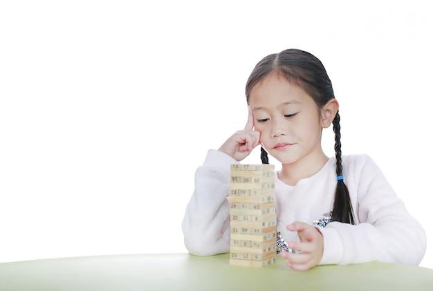 Menina asiática pensando em jogar blocos de madeira torre jogo na sala de aula