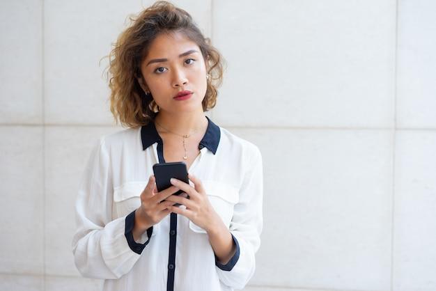 Menina asiática pensativa, navegação web ao ar livre