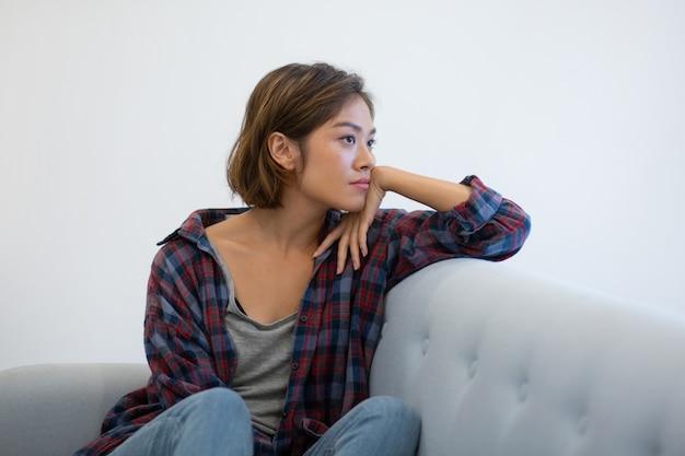 Menina asiática pensativa no sofá que pensa sobre problemas