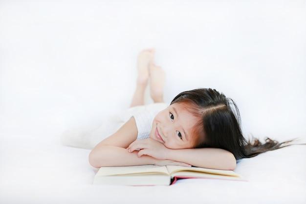 Menina asiática pequena adorável com o livro de capa dura que encontra-se na cama e que olha a câmera sobre o fundo branco.