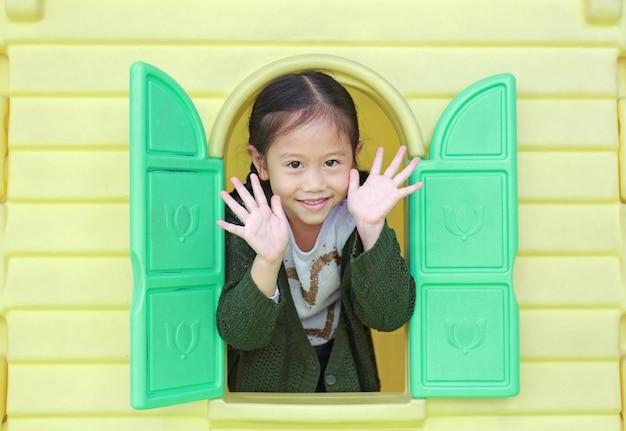 Menina asiática pequena adorável da criança que joga com o teatro do brinquedo da janela no campo de jogos