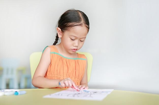 Menina asiática pequena adorável que tira e que pinta com cor da água no papel na sala de crianças