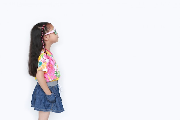 Menina asiática pequena bonita da criança que veste um vestido e óculos de sol do verão das flores isolados com copyspace. conceito de moda e verão. vista lateral.