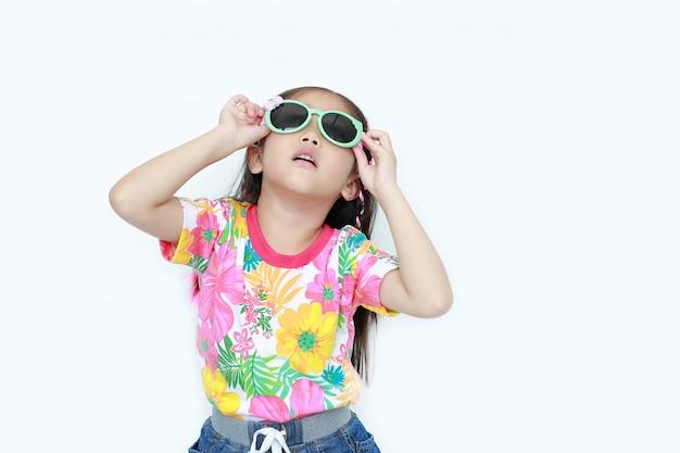 Menina asiática pequena bonita da criança que veste um vestido e uns óculos de sol do verão das flores que olham isolados acima no branco.