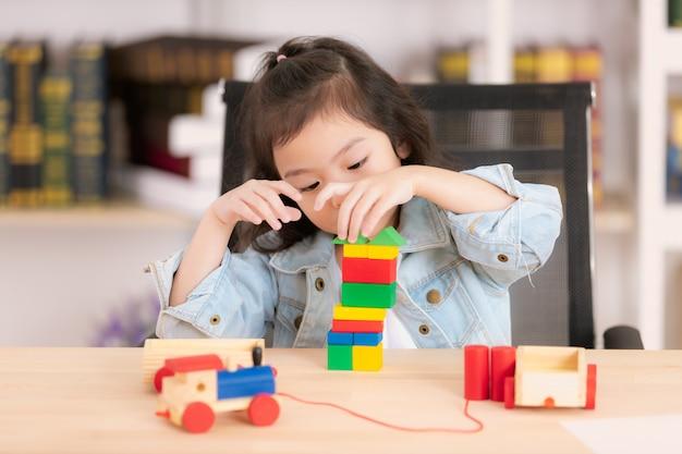 Menina asiática pequena bonito bonita na camisa das calças de brim que joga brinquedos do bloco de madeira na mesa.