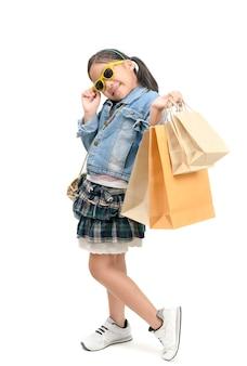 Menina asiática pequena bonito que guarda sacos de compras.