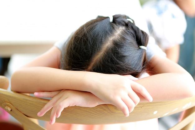 Menina asiática pequena cansado da criança do close-up que dorme na cadeira de madeira.