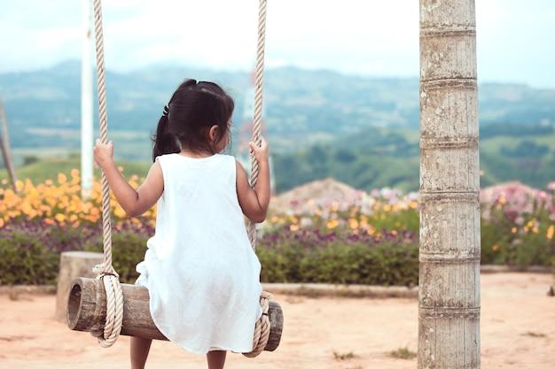 Menina asiática pequena criança pequena sentada em baloiços de madeira e olhando a vista natural no campo de jogos