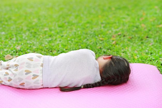 Menina asiática pequena da criança da vista traseira que dorme no colchão cor-de-rosa no gramado da grama verde no jardim do parque do verão.