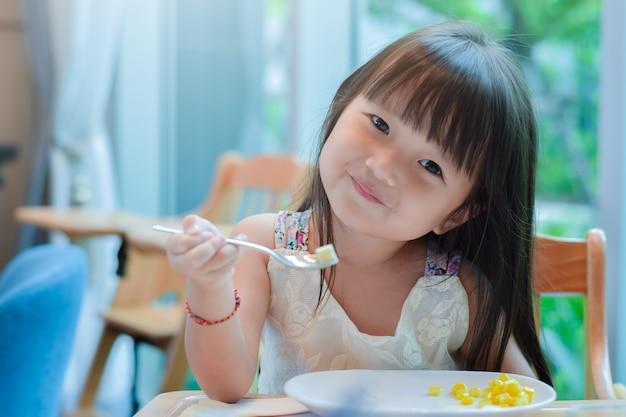 Menina asiática pequena da criança que come o café da manhã na manhã com uma cara de sorriso feliz e que mostra o alimento em uma colher.