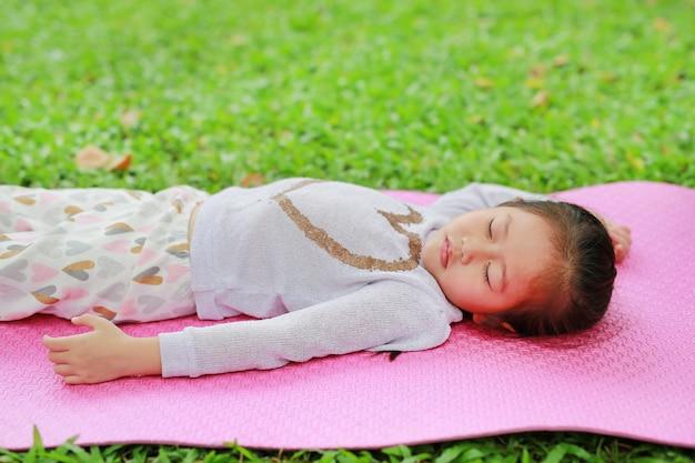 Menina asiática pequena da criança que dorme no colchão cor-de-rosa no gramado da grama verde no jardim do parque do verão.