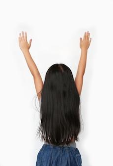 Menina asiática pequena da criança que levanta as mãos isoladas acima. visão traseira.