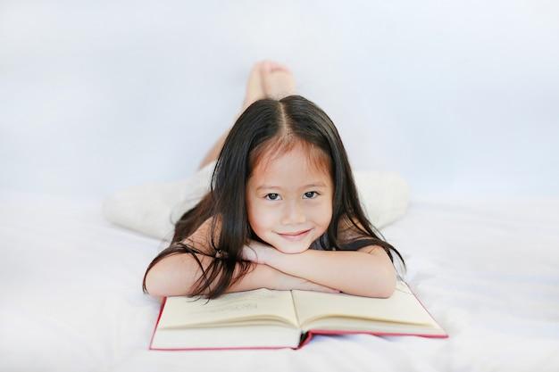 Menina asiática pequena de sorriso da criança com o livro de capa dura que encontra-se na cama e que olha a câmera sobre o fundo branco.