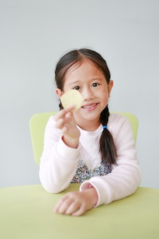Menina asiática pequena de sorriso da criança que come microplaquetas de batata friáveis no branco.