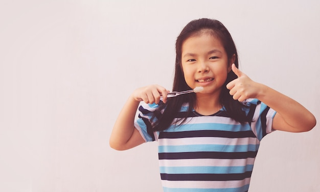 Menina asiática pequena escova de dentes
