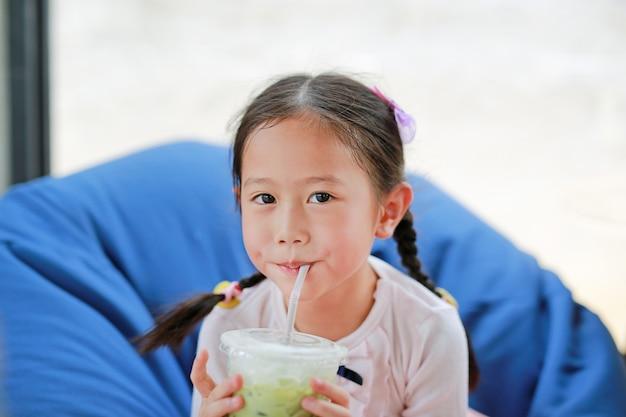 Menina asiática pequena feliz da criança que bebe o chá verde gelado de matcha que encontra-se no sofá no café.