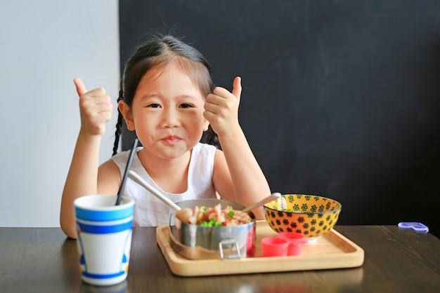 Menina asiática pequena feliz da criança que come o arroz pelo auto no restaurante.