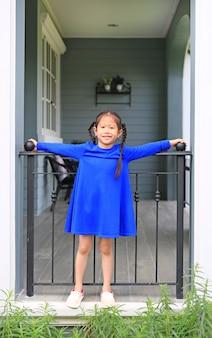 Menina asiática pequena feliz da criança que está em barras do balcão da casa e que olha a câmera na manhã.