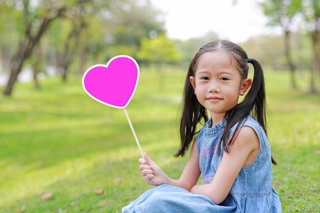Menina asiática pequena feliz da criança que guarda a etiqueta vazia do coração que senta-se na grama verde no jardim exterior.