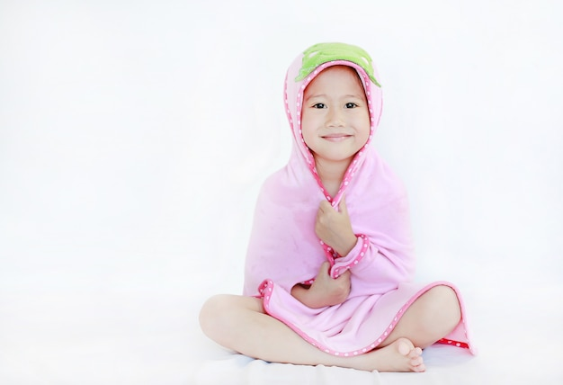 Menina asiática pequena feliz da criança que sorri sob a toalha após o banho que senta-se no fundo branco.
