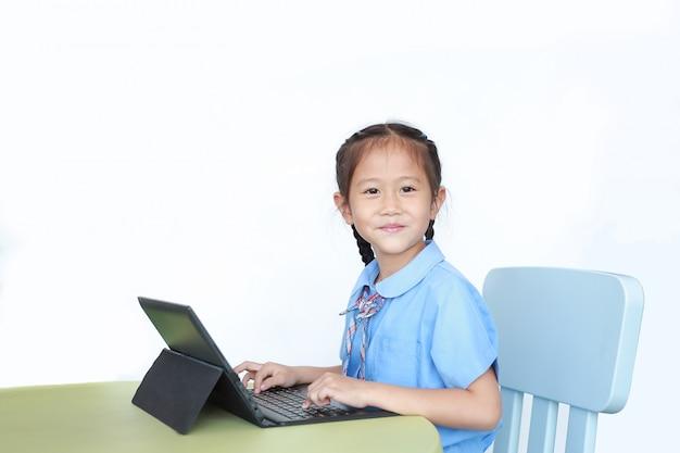 Menina asiática pequena feliz que usa o laptop para fazer trabalhos de casa na mesa.