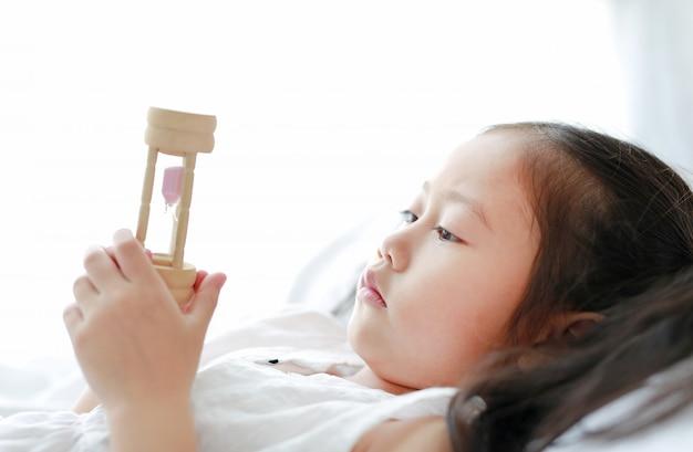 Menina asiática pequena que olha a ampulheta à disposição que encontra-se na cama em casa.