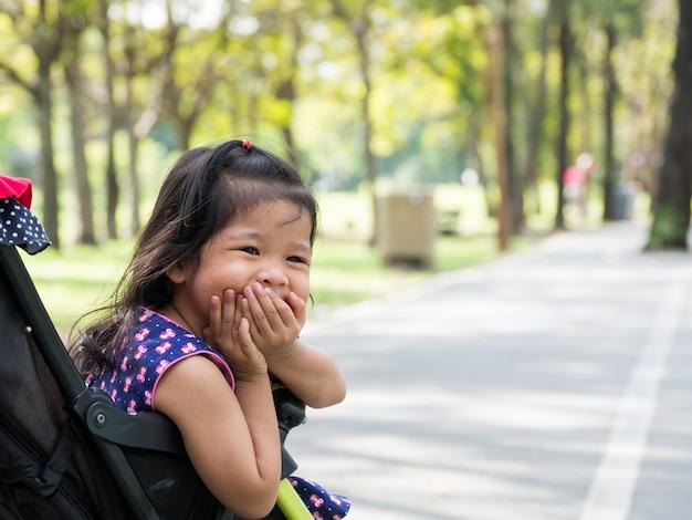 Menina asiática pequena que senta-se em um carrinho de criança no parque público. ela parece feliz, rindo e engasgando.
