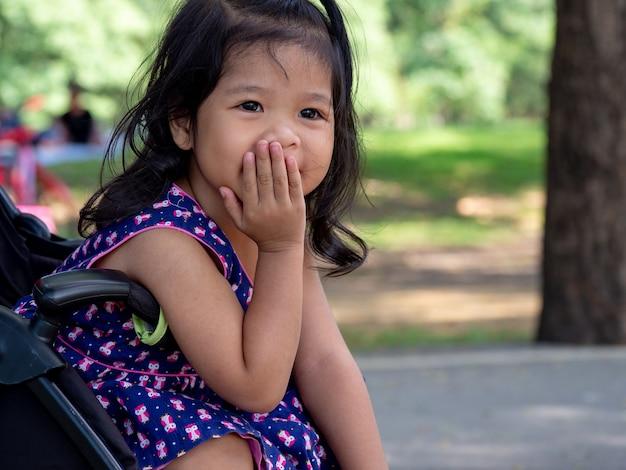 Menina asiática pequena que senta-se em um carrinho de criança no parque público. ela tem que ser sorriso