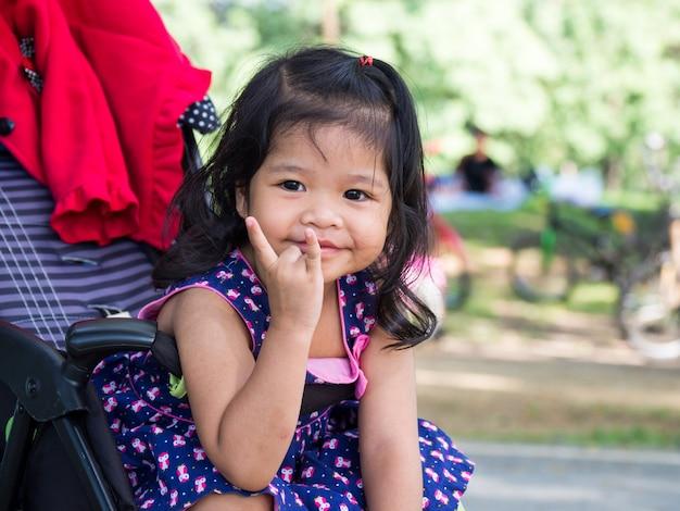 Menina asiática pequena que senta-se em um carrinho de criança no parque público.