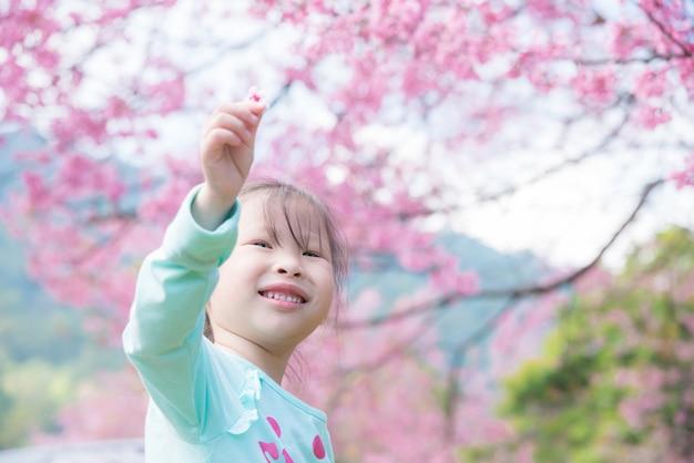 Menina asiática pequena que sorri na frente da árvore de sakura.