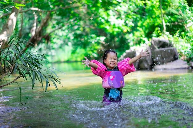 Menina asiática pequena que veste as luvas infláveis que jogam a água da natureza no feriado