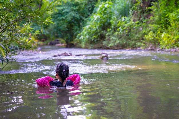 Menina asiática pequena que veste as luvas infláveis que nadam na água da natureza no feriado
