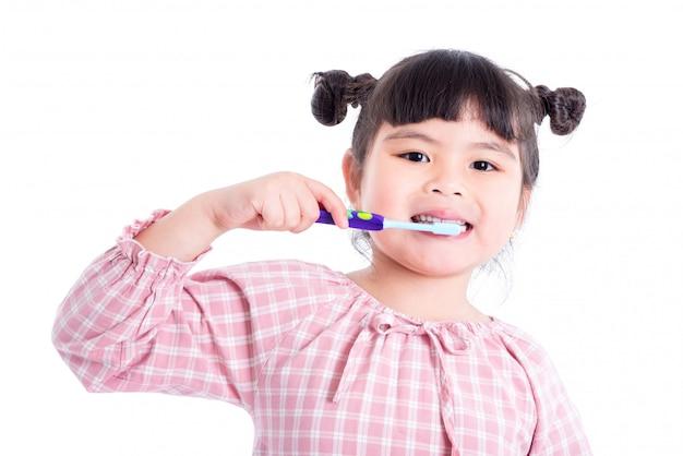 Menina asiática pequena segurando a escova de dentes e sorrisos sobre fundo branco