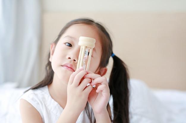 Menina asiática pequena segurando sandglass na mão com olhar através da câmera