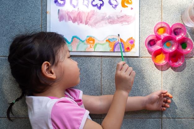 Menina asiática pintando com aquarela sobre papel