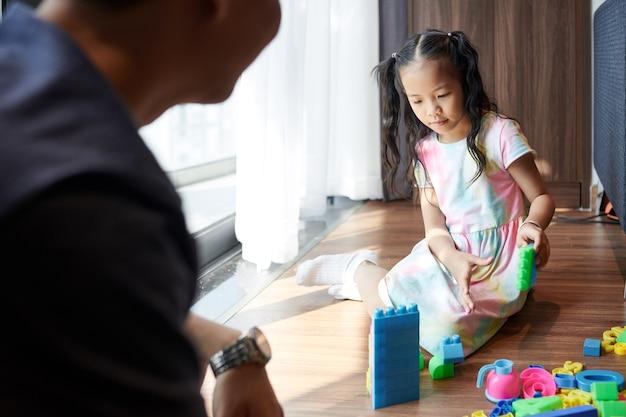 Menina asiática pré-adolescente mostrando a torre do pai que ela fez com blocos de plástico coloridos