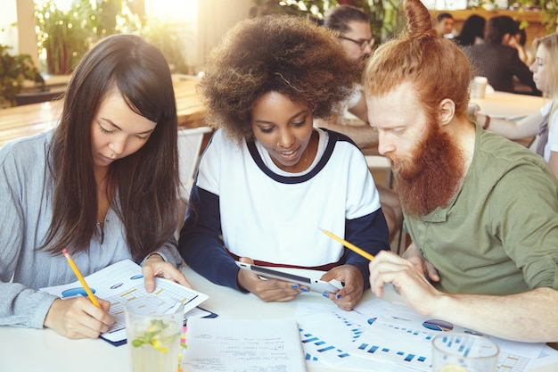 Menina asiática preenchendo papéis com gráficos e diagramas enquanto mulher africana compartilhando ideias com o colega barbudo ruivo no touchpad.