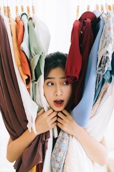 Menina asiática presa em sua bagunça de roupas