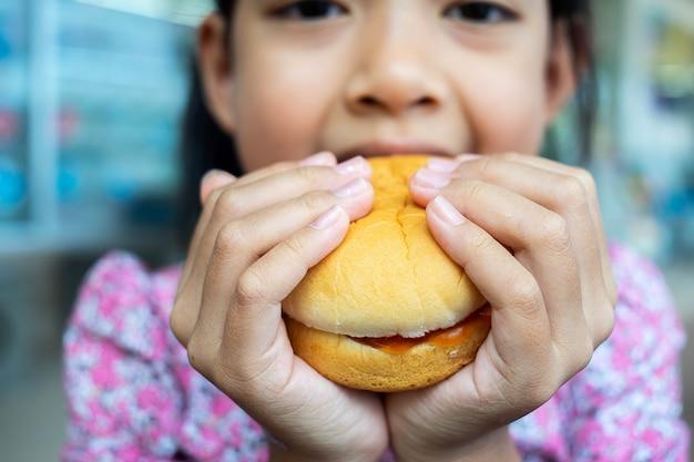 Menina asiática que come um hamburger.