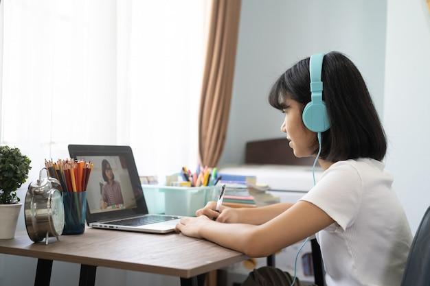Menina asiática que estuda a lição em linha dos trabalhos de casa em casa, conceito em linha da ideia da educação da distância social