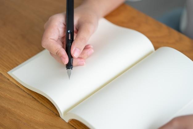 Menina asiática que guarda uma escrita preta da pena em um livro vazio.